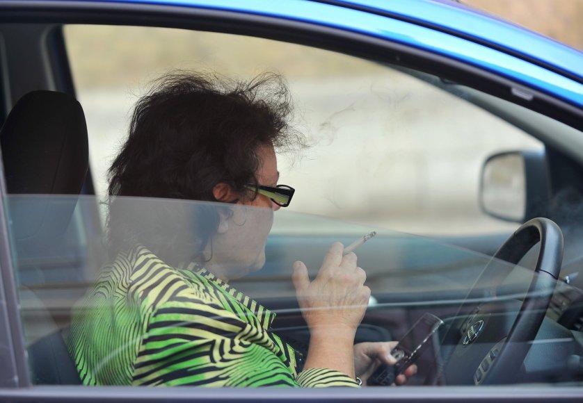 Moteris rūko automobilyje ir naudojasi mobiliuoju telefonu