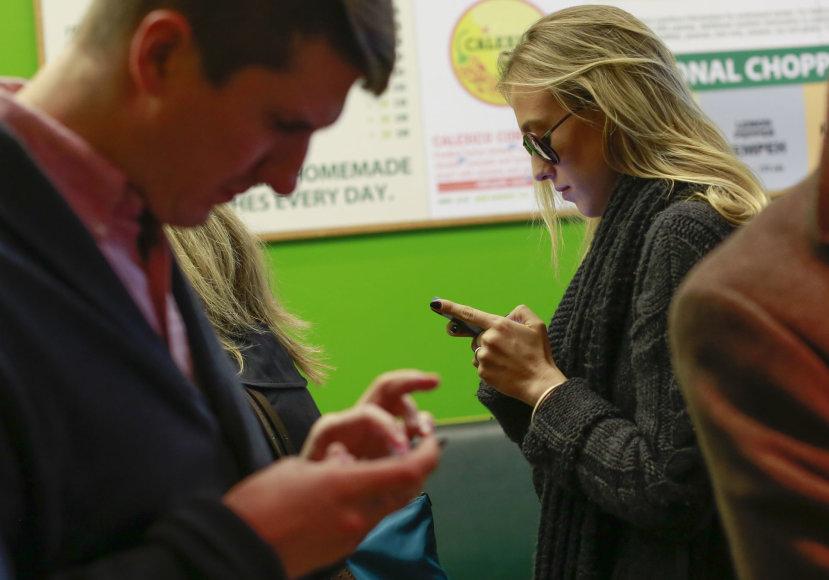 Jauni žmonės prasmegę savo telefonų ekranuose