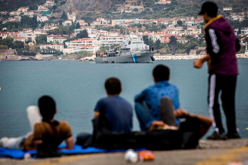 Migrantai stebi, kaip į Lesbo salos uostą karinis laivas atplukdo išgelbėtus jų likimo brolius.