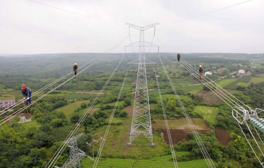 Darbininkai Kinijoje tikrina naujai nutiestą elektros liniją