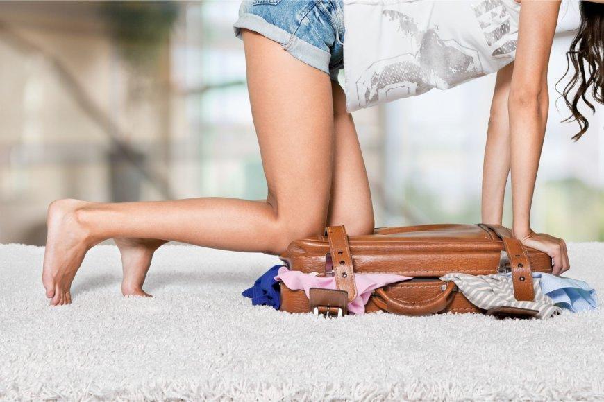 Fotolia nuotr./Moteris stengiasi uždaryti prikrautą lagaminą