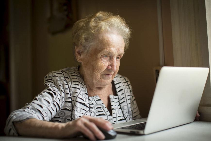 Garbaus amžiaus moteris prie kompiuterio