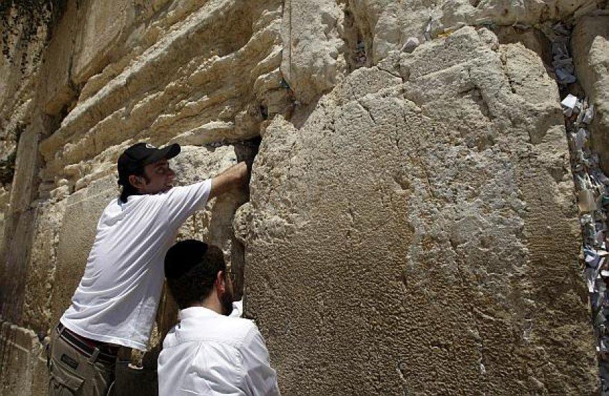 Alonas Niras (kairėje) kiša ritinėlius su maldomis į Raudų sienos plyšį