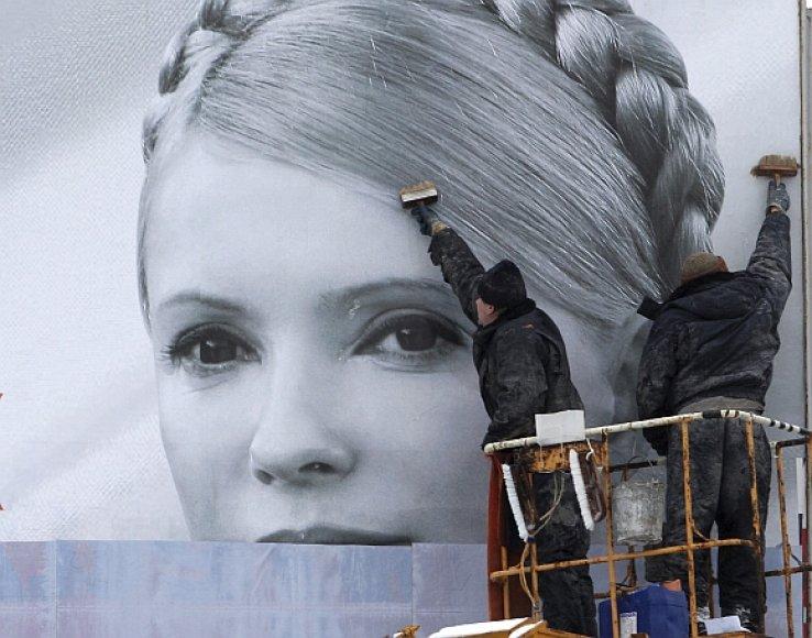 Darbininkai prieš rinkimų savaitgalį uždengia kandidatės Julijos Tymošenko agitacinį plakatą.