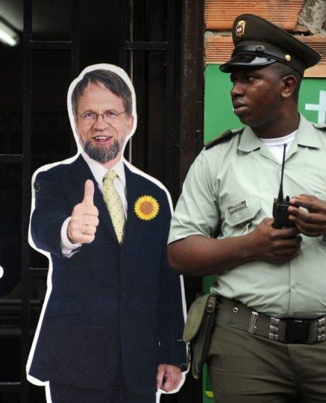 Kolumbijos policininkas stovi prie kartoninio Antano Mockaus.