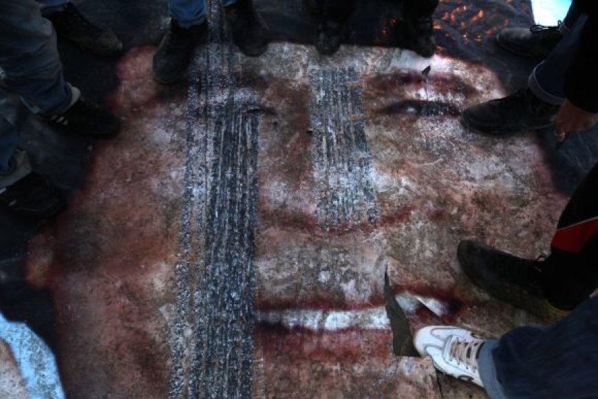 Libijos sukilėliai trypia Muamaro Kadhafi plakatą Bengazyje.