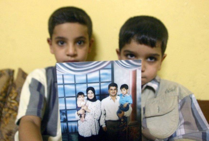 Bahos Mousos sūnūs Hassanas (kairėje) ir Ali rodo nuotrauką, kurioje visa šeima įamžinta kartu su tėčiu.