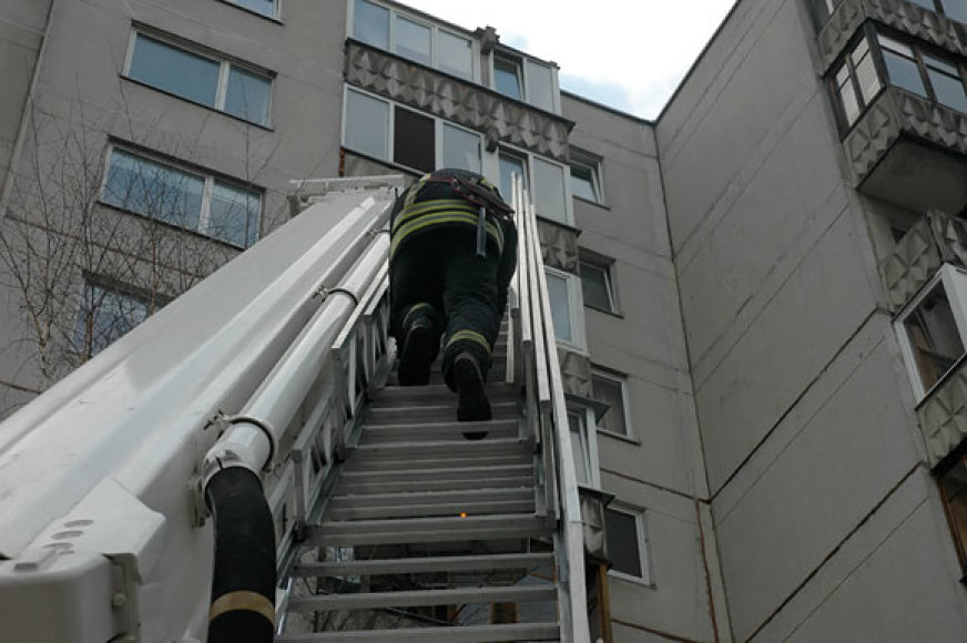 Ugniagesys lipa į degantį butą