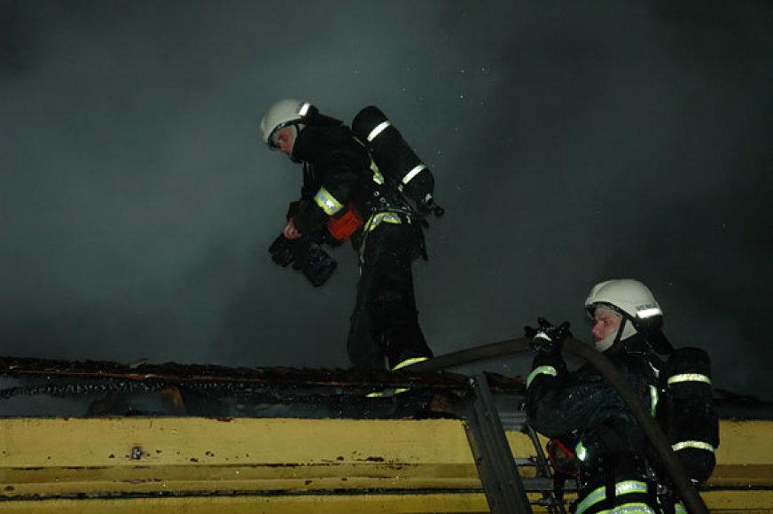 Ugniagesiai ant degančios mokyklos stogo