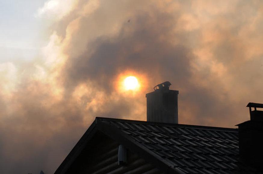 Kylanti saulė pro gaisro dūmus