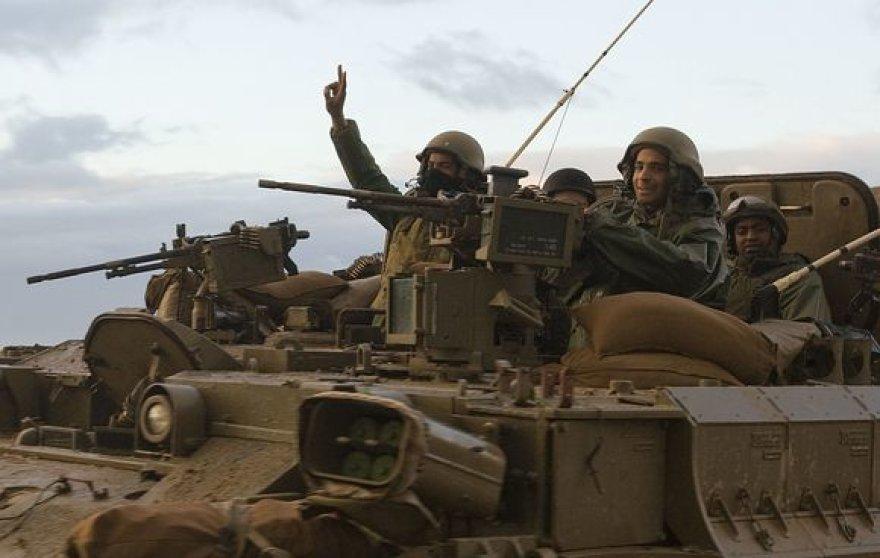Izralio karys rodo pergalės ženklą. Jo šalis sekmadienio naktį paskelbė paliaubas Gazos ruože.