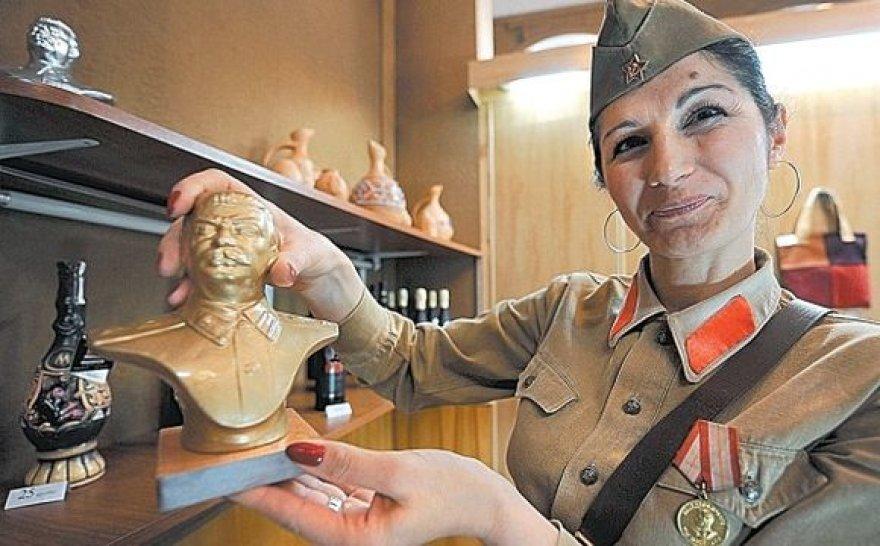 Muziejaus darbuotoja didžiuodamasi rodo Stalino biustą.