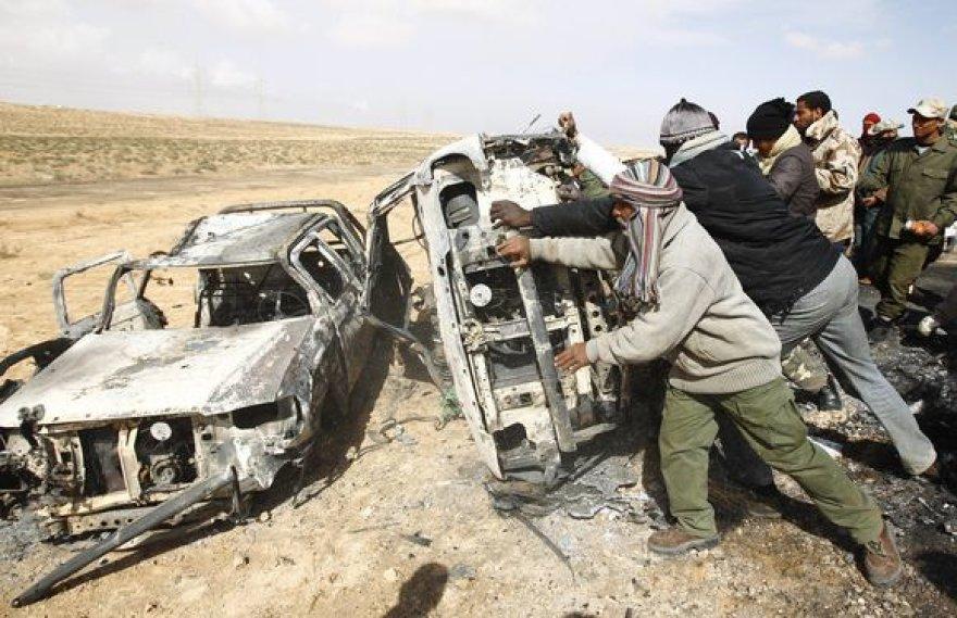 Sukilėliai bando apversti apšaudytus automobilius.
