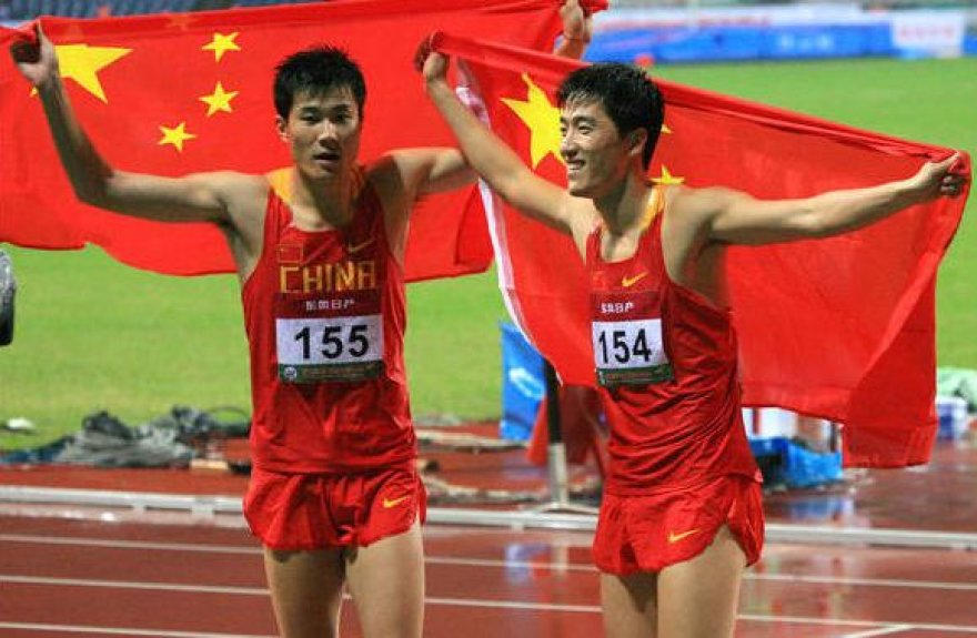 Triumfuoja Kinijos barjerininkai Liu Xiangas (dešinėje) bei Shi Dong Pengas