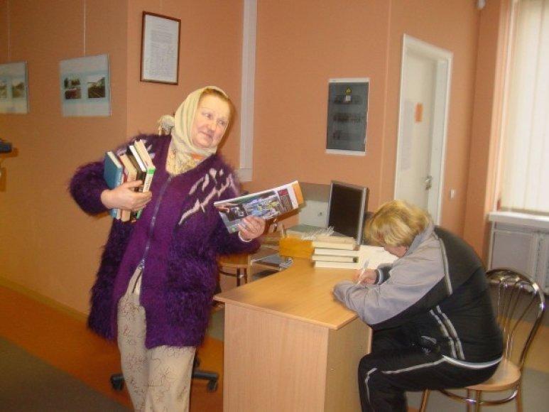 Panevėžio 9–osios vidurinės mokyklos bibliotekininkė D.Jucienė (kairėje) piktinasi dėl išjungto šildymo, bet stengiasi neprarasti humoro jausmo.