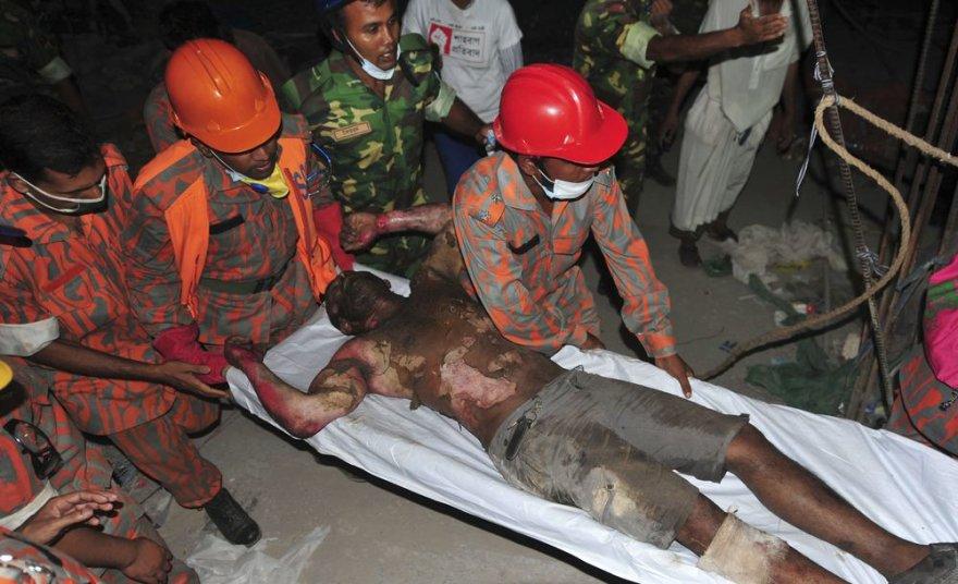 Bangladeše gelbėtojai iš po griuvėsių traukia siuvimo fabriko darbuotojus.