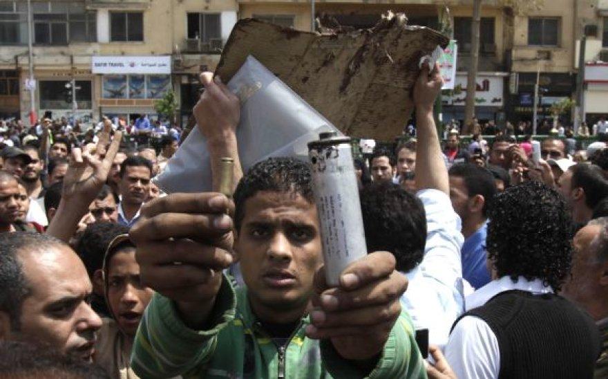 Protestuotojas demonstruoja šovinio tūtelę ir panaudą ašarinių dujų kanistrą.