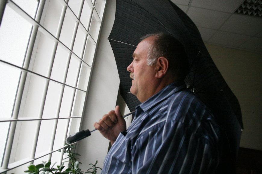 Šiaulių regiono aplinkos apsaugos departamento direktoriaus pavaduotojas A. Pundza nuo žurnalistų slėpėsi po skėčiu.