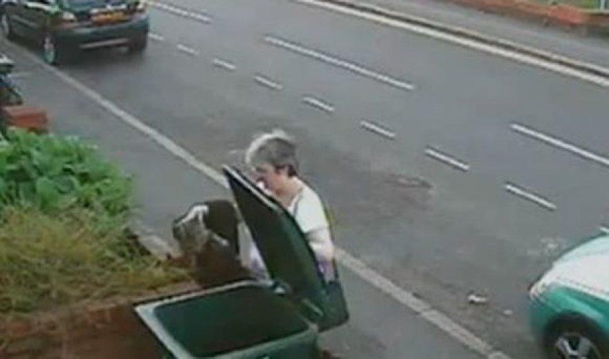 Kadras, kuriame matyti, kaip moteris išmeta katę.