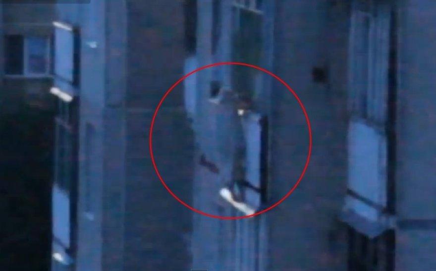 Ant skardinio stogelio 5-ame aukšte stovinti ir į balkono turėklus įsikibusi pensininkė.