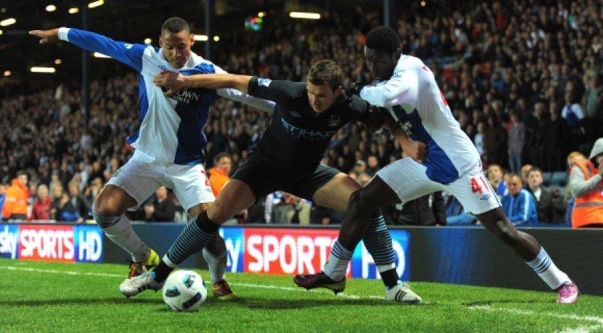 Edinas Džeko (viduryje) grumiasi dėl kamuolio.