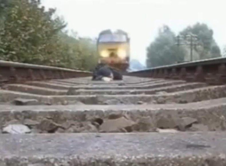 Vyras nusifilmavo, kaip virš jo pravažiuoja traukinys.
