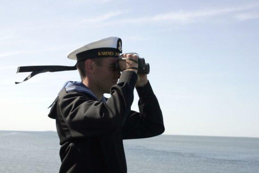 Karinių jūrų pajėgų karys stebi jūrą.