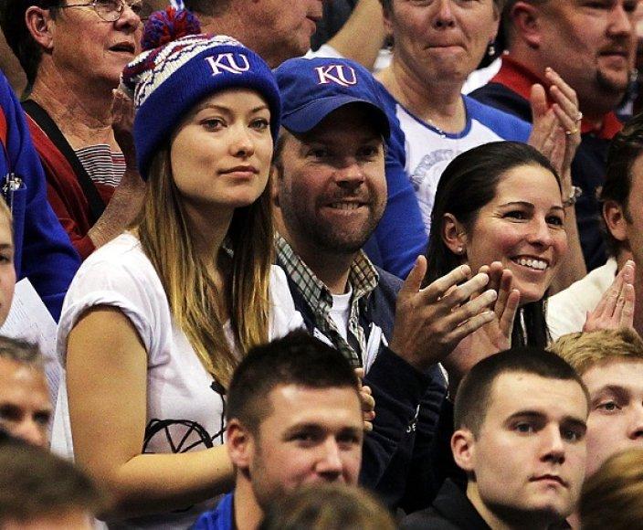 Mėlynomis kepuraitėmis pasipuošę Jasonas Sudeikis ir Olivia Wild stebi krepšinio rungtynes.
