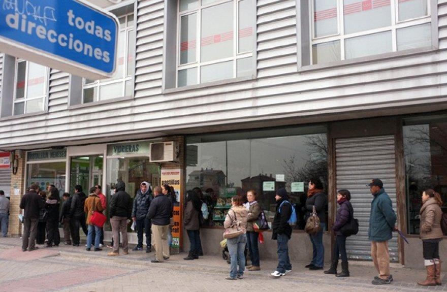 Žmonės laukia prie įdarbinimo biurio Madrido rajone.