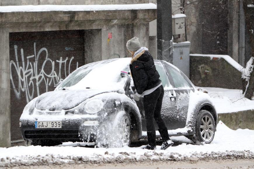 Mergina valo savo automobilį.