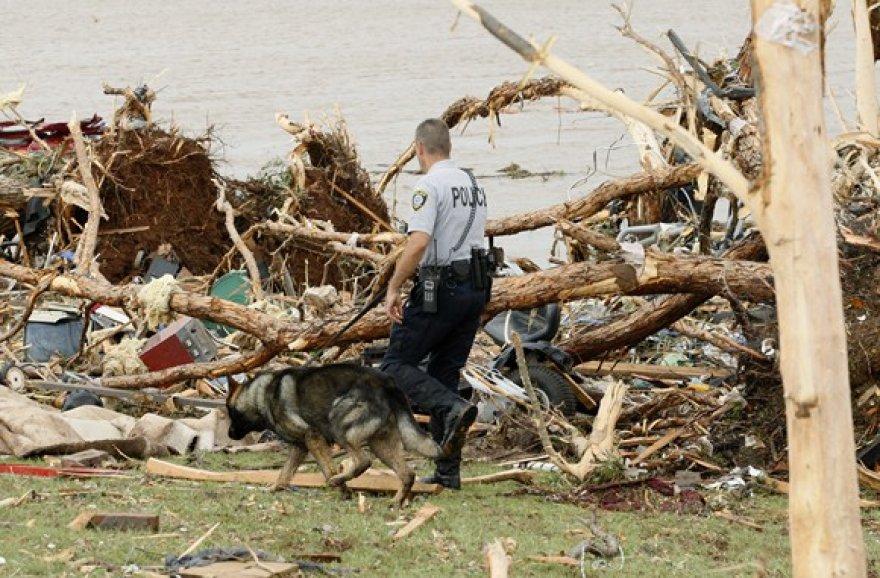 Policininkas su šunimi ieško per tornadą dingusių žmonių.