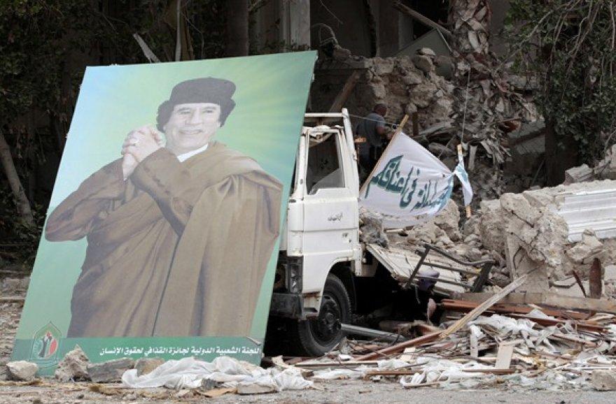 Muamaro Kadhafi plakatas prie sugriuvusio pastato Tripolyje