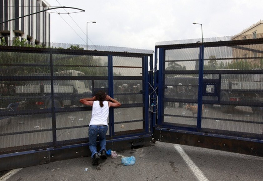 Protestuotojas prie aptverto Graikijos parlamento