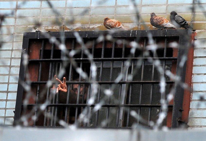 Vyras pro kalėjimo grotas rodo pergalės ženklą.