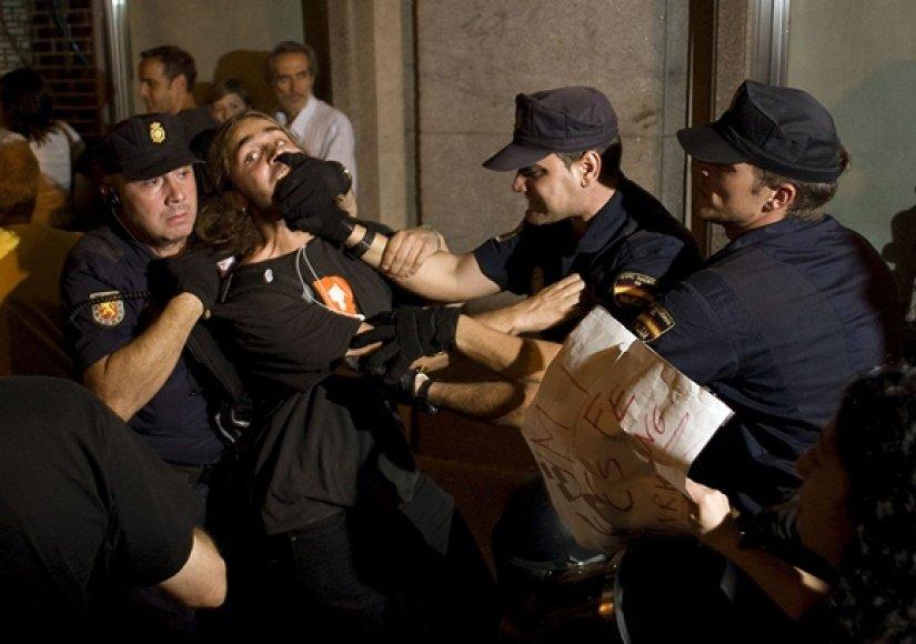 Policininkai sulaikė protestuotoją.