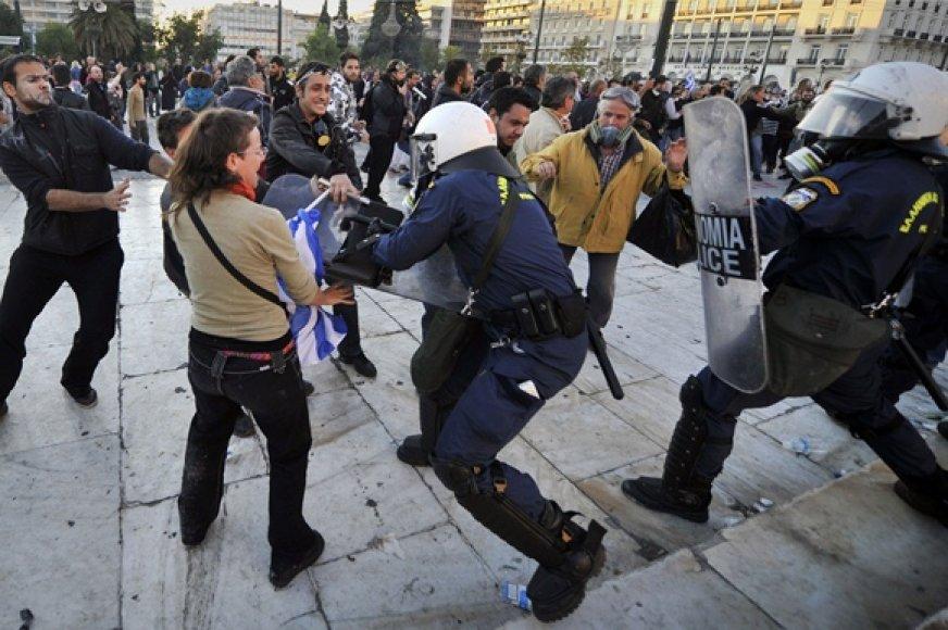 Protestuotojai bando atimti skydą iš policininko.