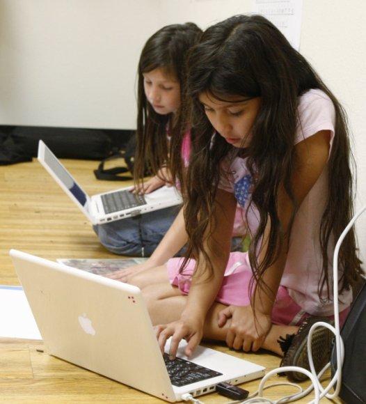 Mergaitės naudojasi kompiuteriu