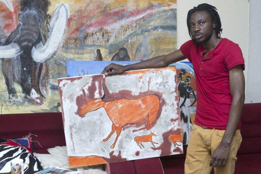 Princas iš Kamerūno prie tapybos paveikslų afrikietiškais motyvais