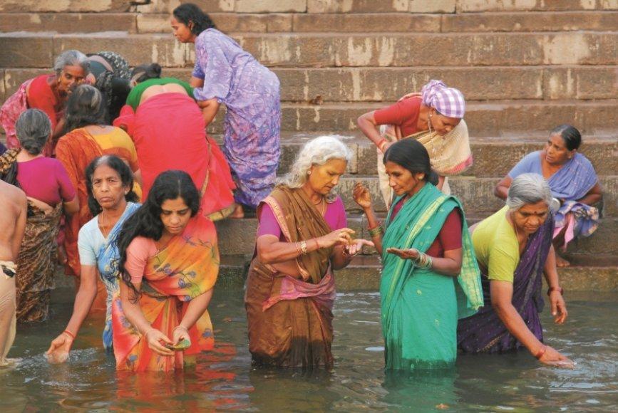 Spalvingos indų moterys prausiasi Varanasyje