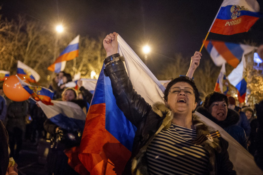 Pro-Russian people celebrate in the central square in Sevastopol, Ukraine, late Sunday, March 16, 2014. Russian flags fluttered above jubilant crowds Sunday after residents in Crimea voted overwhelmingly to secede from Ukraine and join Russia. The United States and Europe condemned the ballot as ill