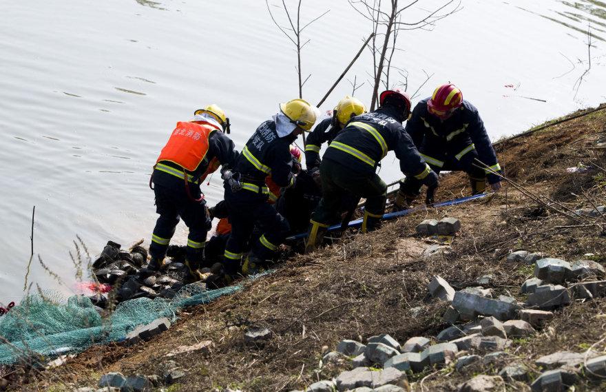 Gelbėtojai iš ežero traukia žuvusiųjų kūnus.