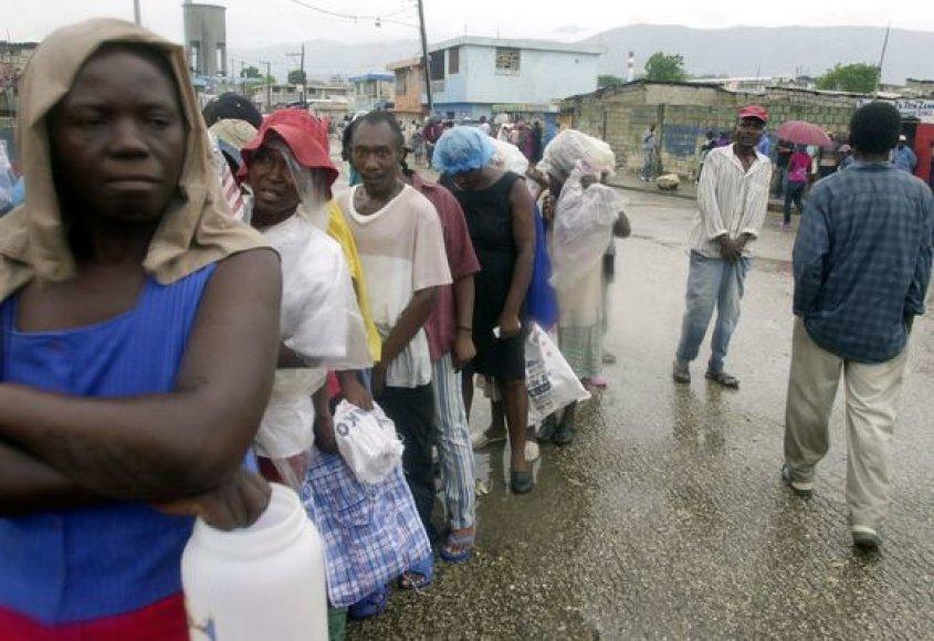 Žmonės stovi eilėje prie maisto davinio.