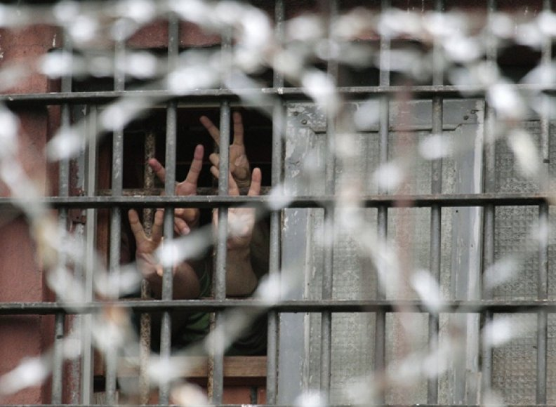 Pergalės ženklus pro kalėjimo grotas rodantys sulaikyti protestuotojai