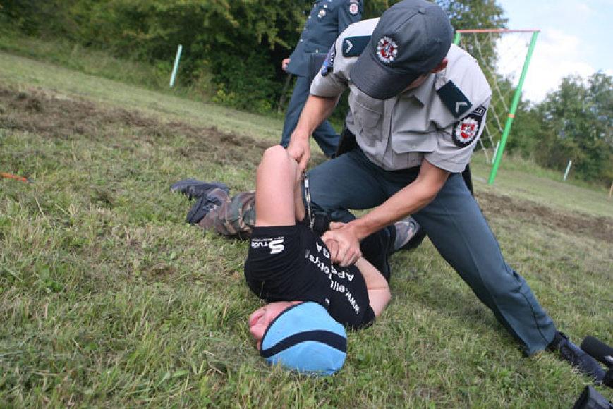 Policininkas sulaiko nusikaltėlį.