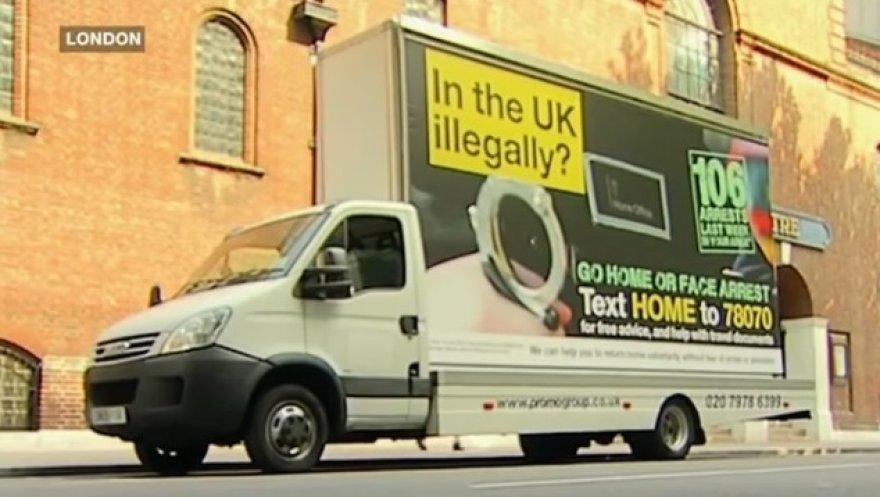 """Reklaminiai plakatai skelbia: """"Go home or face arrest"""" (""""Važiuok namo arba būsi suimtas"""")"""