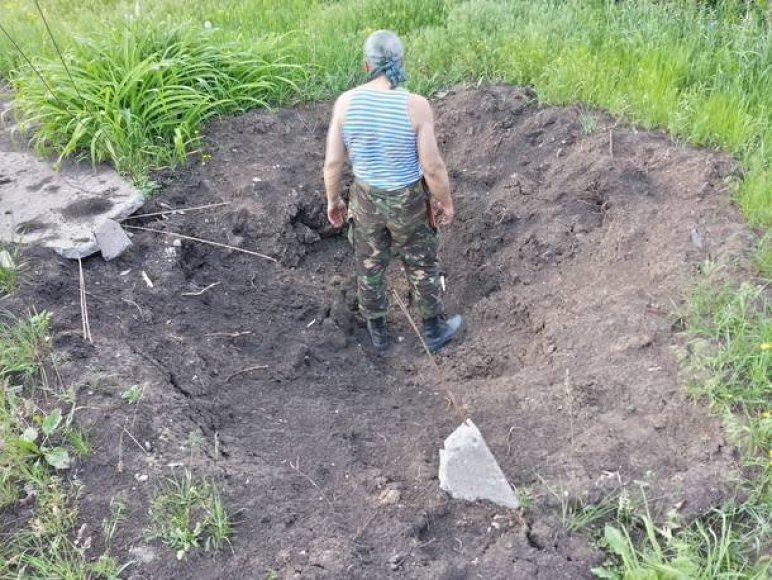 Ukrainos karys stovi haubicos smūgio paliktame krateryje.
