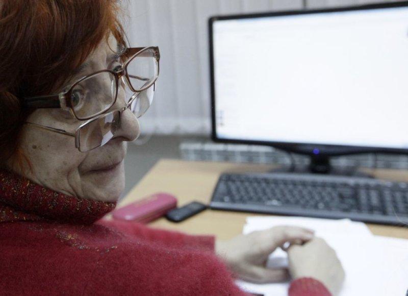 Pagyvenęs žmogus dirba su kompiuteriu