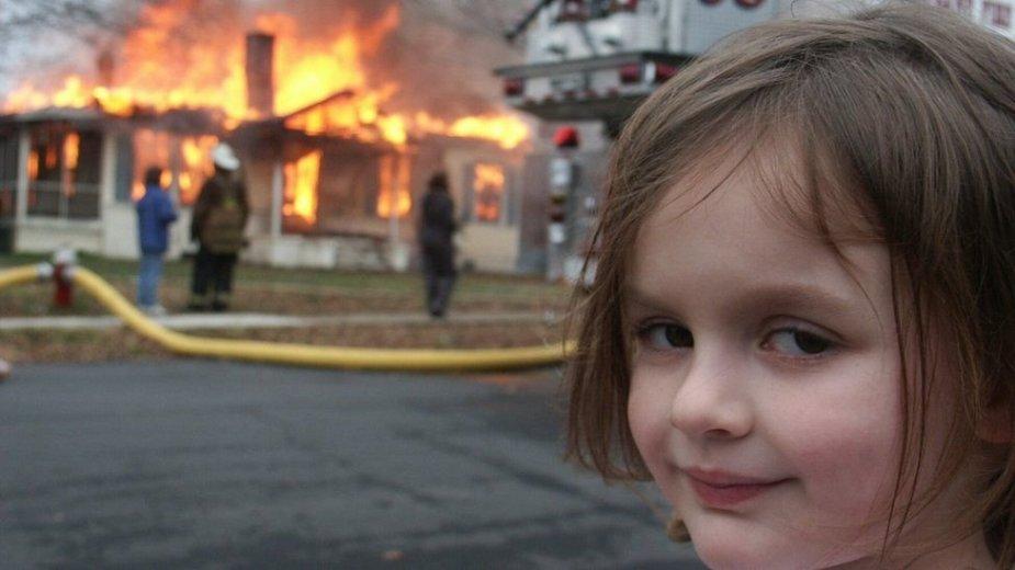 Į degantį namą žvelgiančios mergaitės memas