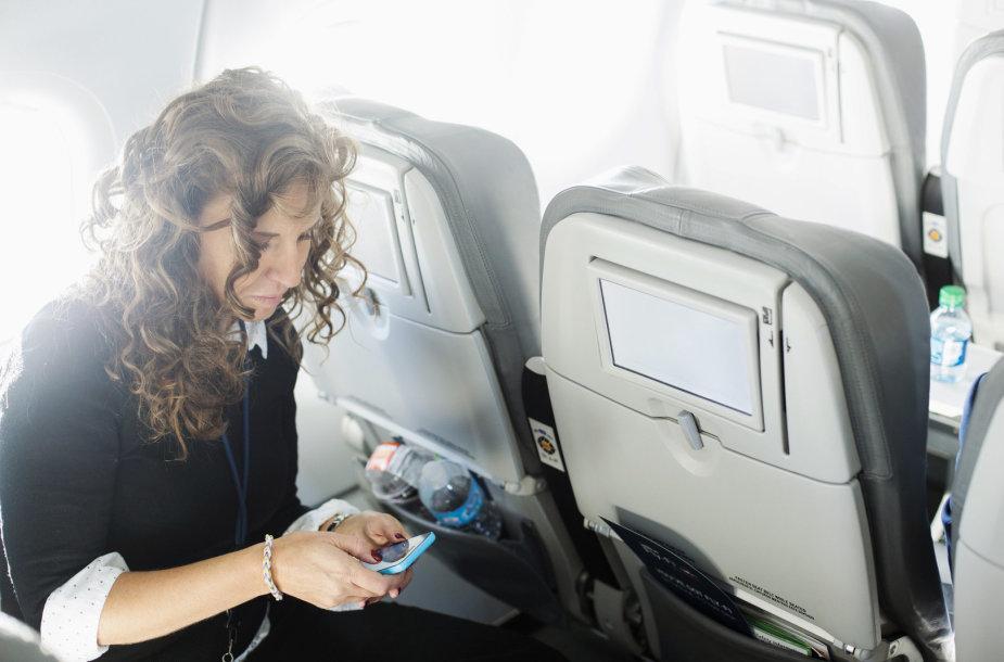 Moteris naudojasi išmaniuoju telefonu