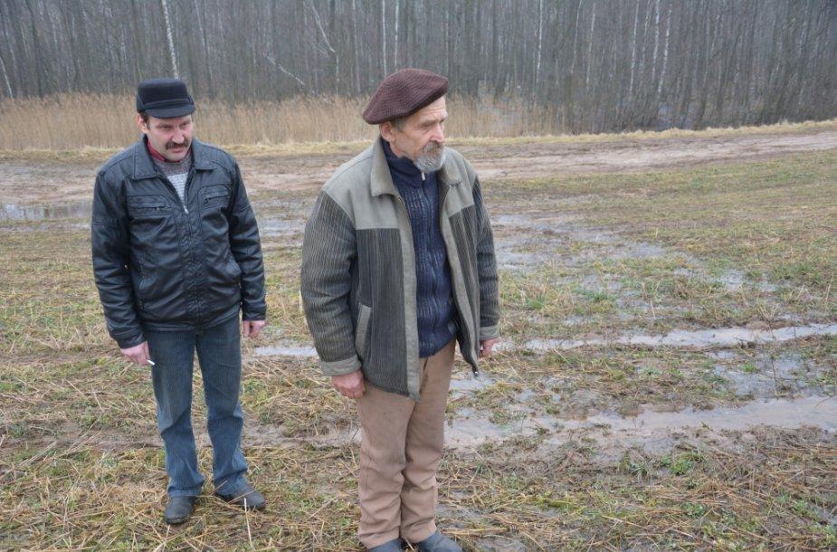 Algirdas Milukas (kairėje) ir jo kamynas Juozas Volungevičius stebi, kaip upelis, susidarantis keletą mėnesių per metus, per kelią teka iš Bakšių ežero į Teizų.